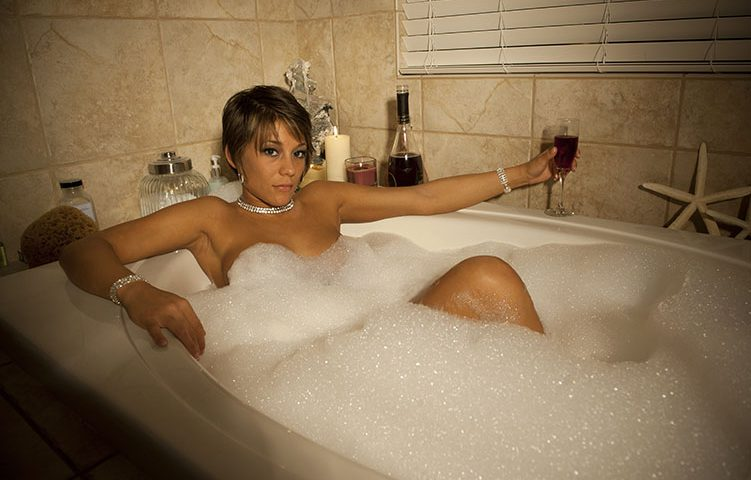 Implied nude adult female in bubble bath with wine