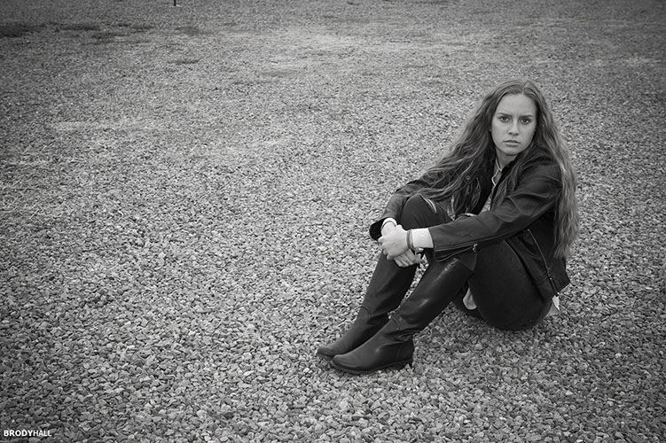 Young adult female model sitting on gravel road