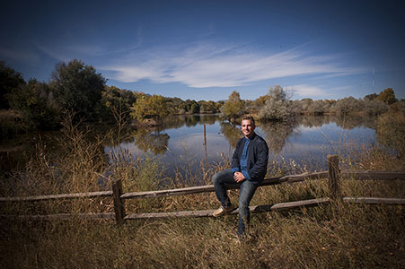 Senior portrait of male sitting on wooden fence by a lake in Fountain, CO
