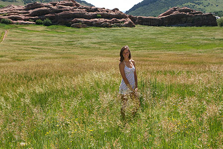 Young female in short dress standing in grassy field