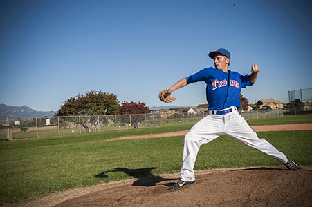 High school senior on pitcher's mound, pitching a baseball wearing blue jersey