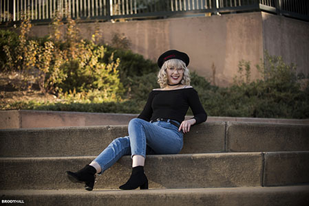 High school senior portrait of blond female wearing black top and jeans posing on cement stairs in Denver, CO