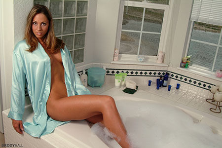 Blond woman wearing sea foam green satin robe sitting on the edge of a bubble bath