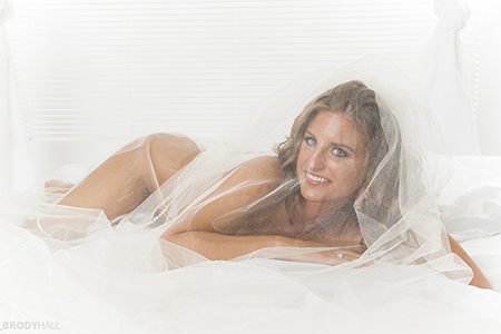 implied nude bride in veil laying on bed in studio