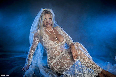 Blond bride in long white lace lingerie and veil, in studio.
