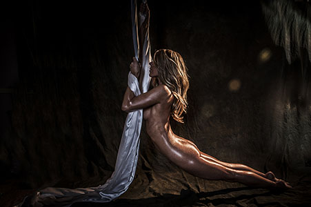 Implied nude model hanging by aerial silk in studio