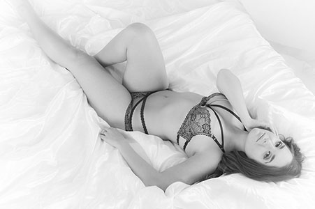 black and white photo of woman laying in bra and panties on white bed.