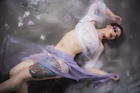 Slender woman laying in fog in white and purple sheer material and flowers