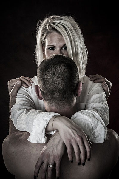Blond woman looking over head of husband
