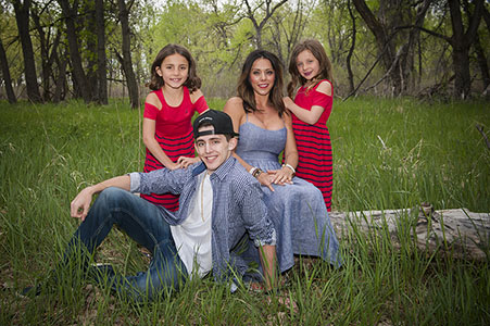 Mom and three children dressed in red and blue in Cherry Creek Reservoir.