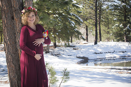 Maternity photo of mother in red dress in the snow at Fox Run Park, Black Forest, CO