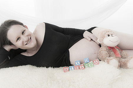 Pregnant mom in photo studio laying down with blocks spelling baby's name