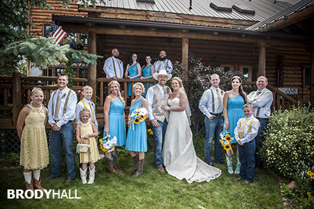 Large bridal party posed in front of cabin at Casey's Barn in Colorado