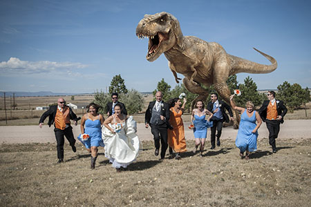 Bridal party running from a T-Rex