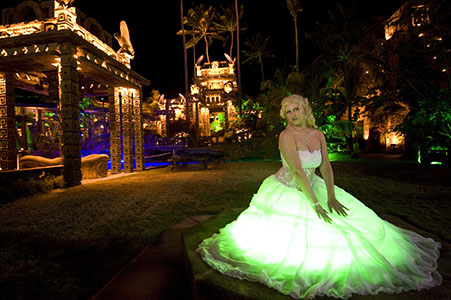 Bride in wedding gown kneeling above a green light, Nygard Cay in the background.