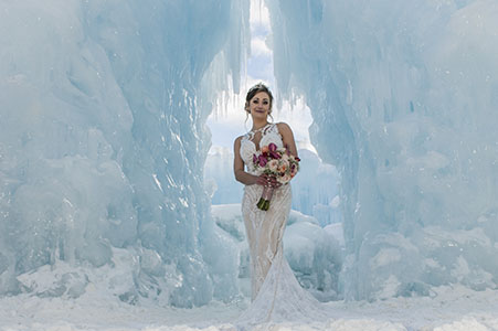 Bride in wedding gown holding a bouquet at the Ice Castle in Dillon, CO