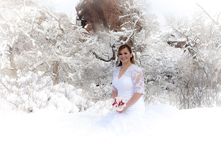 Bride in wedding gown kneeling in the snow at Red Rocks Park in Colorado