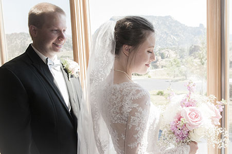 Bride and groom at the window of Rocky Mountain Evangelical Church.