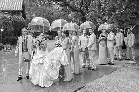 Bridal party lining up with umbrellas, for a wedding down in Florida