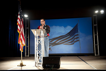 Adult male singing the National Anthem before an Ameriplan Convention in Dallas TX