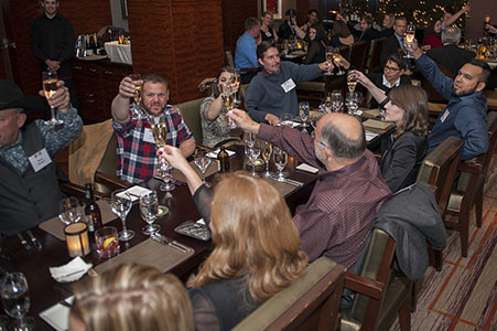 Guest raising their glasses at a business Christmas party at the Edge restaurant in the Four Seasons in Denver, CO
