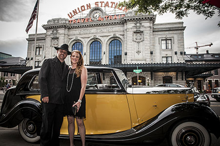 A couple standing in front of a classic Rolls Royce at the Great Gatsby party for Traveler's Haven employees.