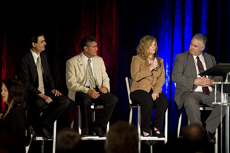 A panel on stage answering questions during a corporate convention