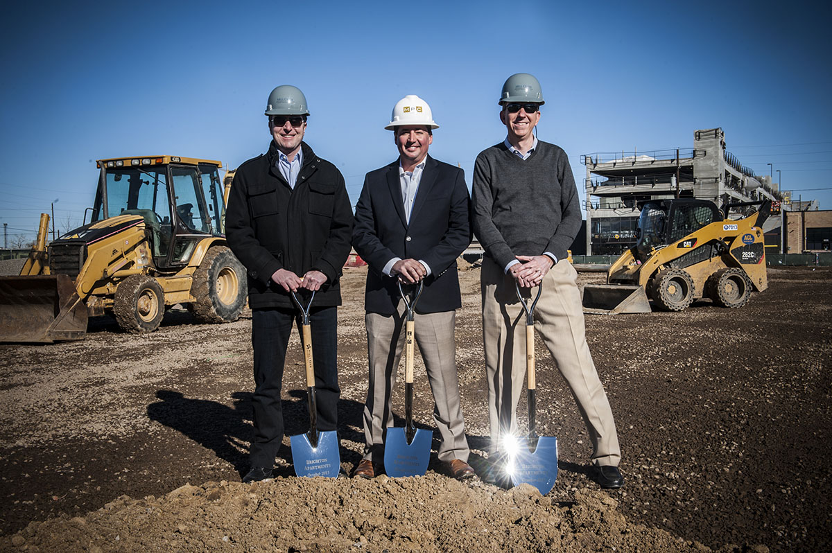 Three employees of MPC construction with shovels during a ground breaking ceremony.