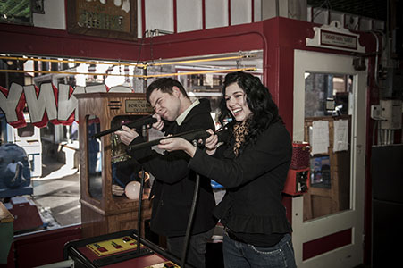 Engaged couple playing a game in the Penny Arcade in Manitou Springs, CO