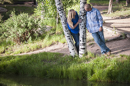 Engaged couple standing by aspens in Fox Run Park, Black Forest, Colorado.