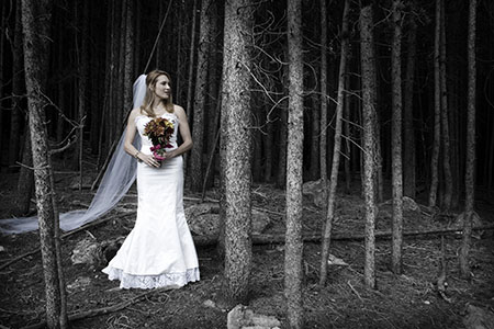 Bride in gown and bouquet standing in woods