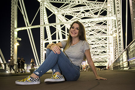 Young woman sitting on Pedestrain bridge in downtown Nashville, TN