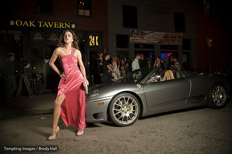 Adult female in long pink evening gown standing next to a silver porsche downtown Denver