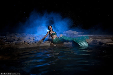 female mermaid with green bra and tail, with blue back light and mist, sitting at edge of pool in Mt. Princeton Hot Springs, CO