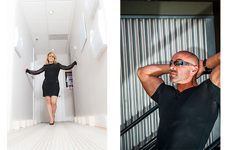 Adult female in black dress posing in white hallway, adult male posing in sunglasses