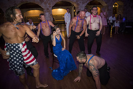 Topless groomsmen dancing for the bride at Baldoria on the Water wedding venue.