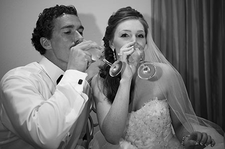 Black and white image of bride and groom drinking champagne at the Marriott in the Nassau Bahamas.