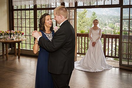 Groom dancing with his mother while bride watches at Historic Crag's Lodge in Estes Park, CO