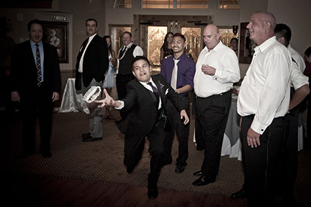 Single men at reception catching the garter