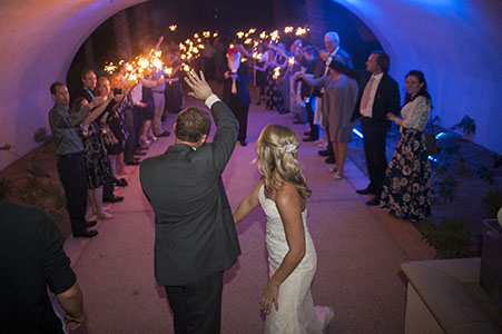 Wedding couple waving to guest in the sparkler line at Reflection Bay Golf Club - Lake Las Vegas