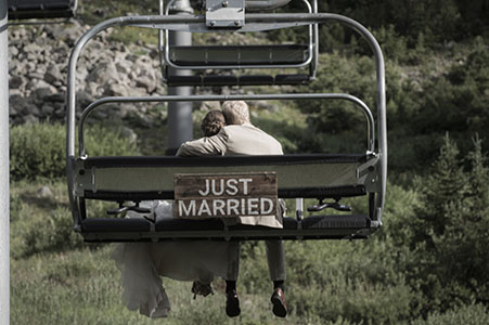 "Wedding couple and ""just married"" sign, riding the gondola at Arapaho Basin ski resort, in Breckenridge, CO"