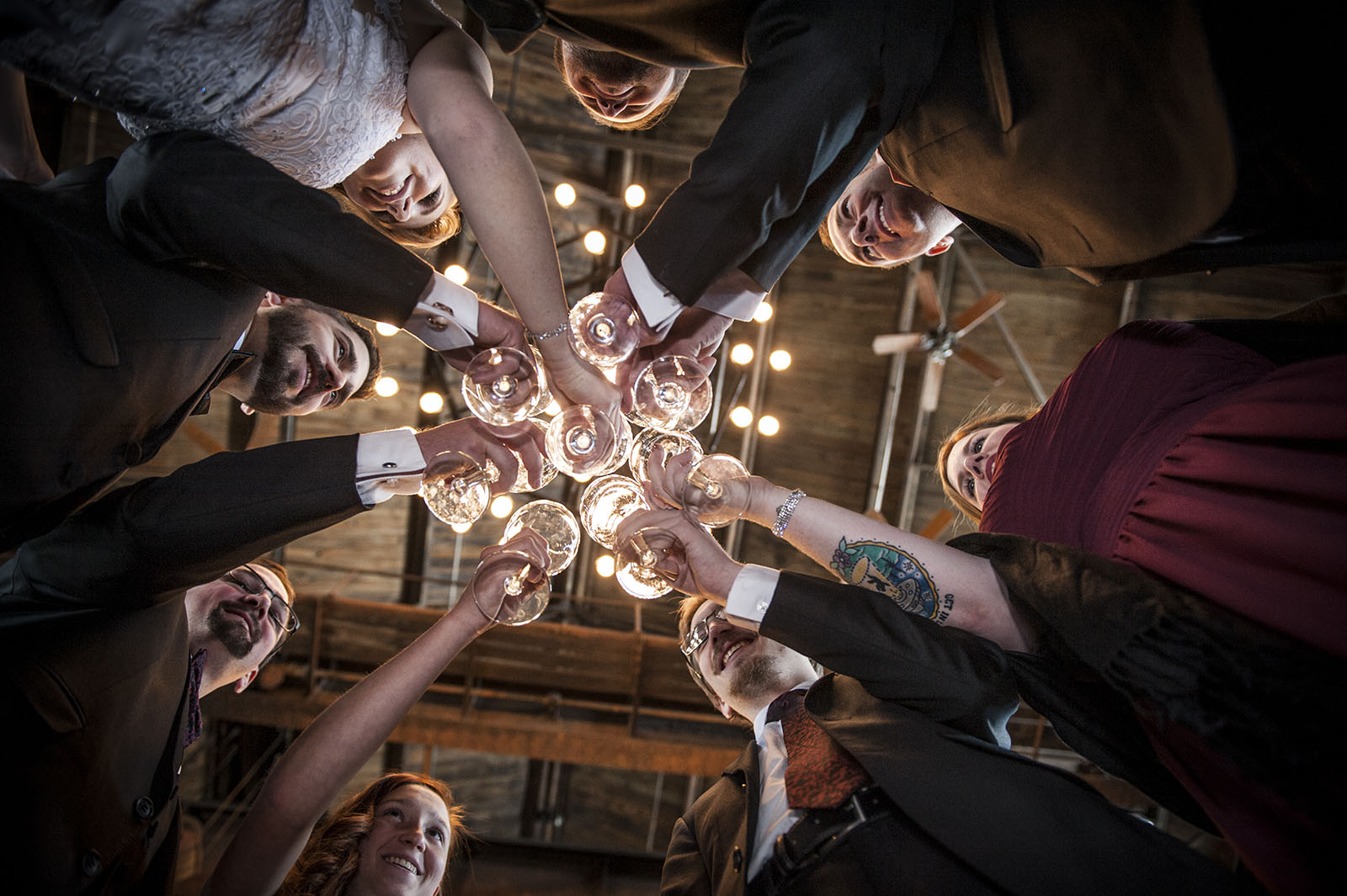 Bridal party clinking glasses at Mile High Station in Denver, CO, photographed from below