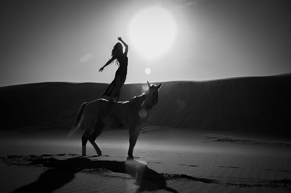 Female model standing on horse in the Great Sand Dunes National Park
