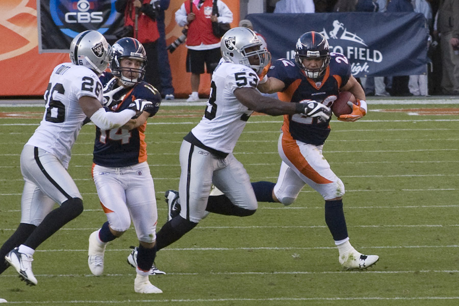 Denver Bronco running back pushing through the Raider's defense.