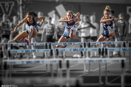 Three girls running hurdles at Valor High School