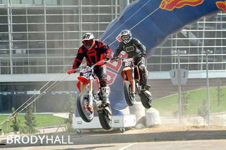 Two competitors jumping a hill at a dirt bike race