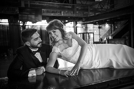 Bride and groom posing on a bar