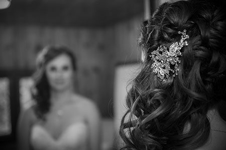 Bridal hair brooch with bride looking in mirror