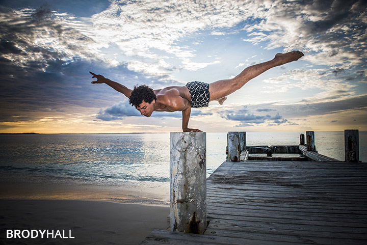 Male acrobat performing on a pier at Club med in the Turks & Caicos islands