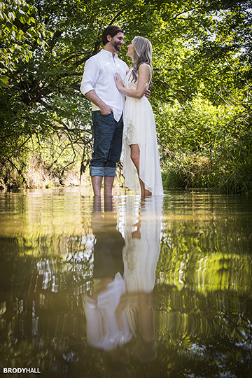Engagment photo of couple standing in stream